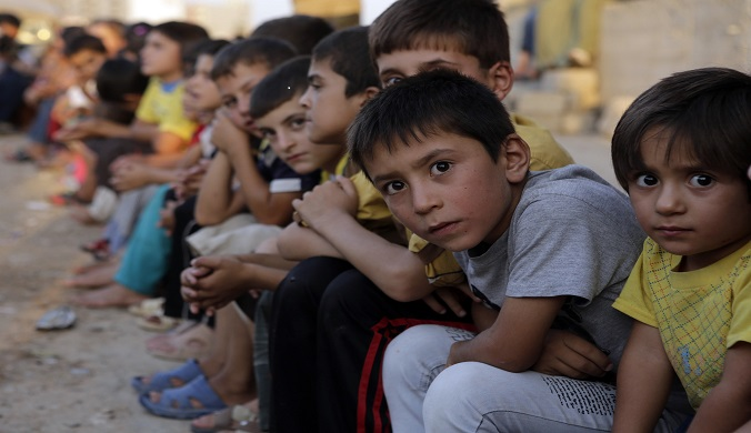 Displaced children from the minority Yazidi sect who fled the violence in the Iraqi town of Sinjar, wait for aid at an abandoned building that they are using as their main residence, outside the city of Dohuk